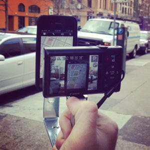 An iPhone is geared to film a street.