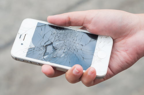 Man holds smartphone with cracked screen
